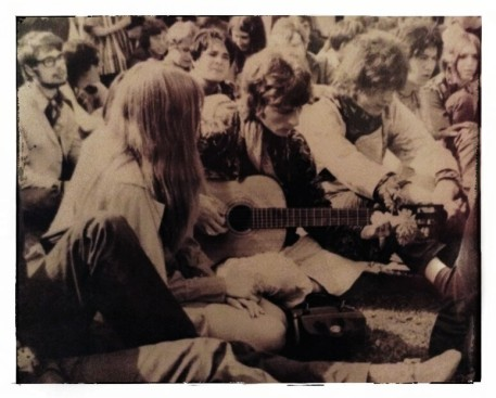 Picture of the Victoria Park Lve-in with Annie Williams facing Rog playing the guitar. Next to him is Mick Pini and behind, looking very dapper is Terry Wilford.