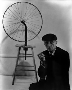 Duchamp with his bicycle wheel mounted on a stool.