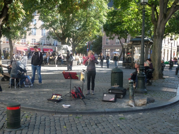 Busker in Brussels. You need a licence and can only play in certain places.